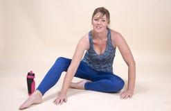Mulher que senta-se em um assoalho do gym com garrafa de água fotos de stock royalty free