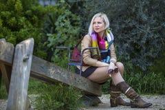 Mulher que senta-se em um balanço de madeira velho no parque Imagens de Stock Royalty Free