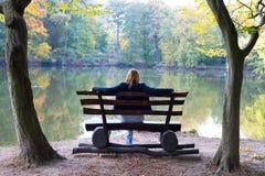 Mulher que senta-se em um banco imagem de stock