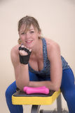 Mulher que senta-se em um banco do treinamento do gym imagem de stock