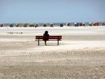 Mulher que senta-se em um banco na praia do Mar do Norte Foto de Stock Royalty Free