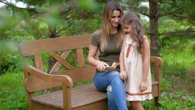 A mulher que senta-se em um banco remove o smartphone após a chegada da criança A menina vem a sua mãe e senta-se video estoque