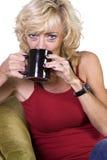 Mulher que senta-se em um café bebendo da cadeira Imagens de Stock