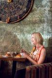 Mulher que senta-se em um café e em um café da bebida Foto de Stock Royalty Free