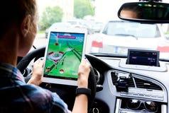 A mulher que senta-se em um carro e que joga um Pokemon vai jogo Fotografia de Stock Royalty Free