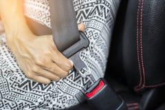 Mulher que senta-se em um carro que veste um cinto de segurança fotos de stock
