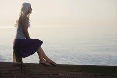 Mulher que senta-se em um pacote de madeira na praia Imagem de Stock Royalty Free