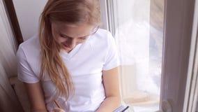 A mulher que senta-se em um peitoril da janela e escreve em seu diário ou jornal vídeos de arquivo