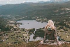 Mulher que senta-se em um pico de montanhas ao olhar em um vale enorme em Noruega imagem de stock royalty free