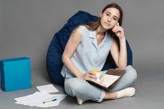 Mulher que senta-se em um saco do descanso e que guarda um caderno nas mãos Isolado no fundo cinzento Fotos de Stock