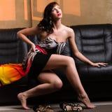 Mulher que senta-se em um sofá de couro fotografia de stock