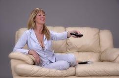 Mulher que senta-se em um sofá que guarda um controlador remoto para uma tevê imagens de stock