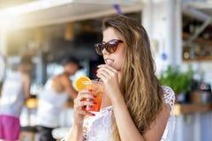 Mulher que senta-se em uma barra da praia e que aprecia um aperitivo imagens de stock royalty free
