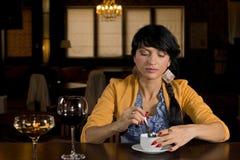 Mulher que senta-se em uma barra que come o café foto de stock royalty free