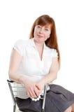 Mulher que senta-se em uma cadeira Fotos de Stock