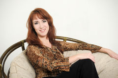 Mulher que senta-se em uma cadeira Fotografia de Stock Royalty Free