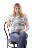 Mulher que senta-se em uma cadeira Imagens de Stock