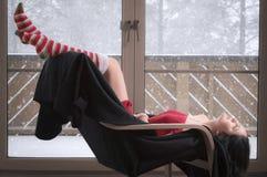 Mulher que senta-se em uma cadeira de cabeça para baixo Imagens de Stock Royalty Free