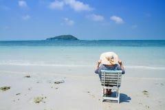Mulher que senta-se em uma cadeira de praia que aprecia um dia de verão no beac fotografia de stock