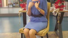 Mulher que senta-se em uma cadeira que fala, gesticulando video estoque