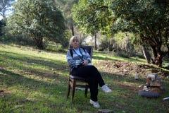 Mulher que senta-se em uma cadeira na floresta Fotos de Stock