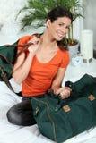 Mulher que senta-se em uma cama com bagagem fotografia de stock royalty free