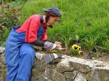 A mulher que senta-se em uma parede de pedra e regula o jardim Imagens de Stock Royalty Free