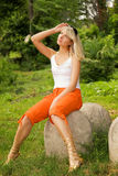 Mulher que senta-se em uma pedra Fotos de Stock Royalty Free
