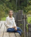 Mulher que senta-se em uma ponte de madeira Foto de Stock Royalty Free