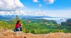 Mulher que senta-se em uma rocha e que aprecia a vista bonita na ilha de Vancôver, Columbia Britânica, Canadá Fotos de Stock