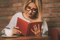 Mulher que senta-se em uma tabela que lê um livro Fotos de Stock