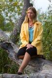 Mulher que senta-se na árvore caída Fotos de Stock Royalty Free
