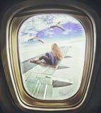 Mulher que senta-se na asa e nos olhares do avião de passageiros em golfinhos imagem de stock royalty free