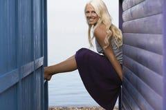 Mulher que senta-se na balaustrada da cabine da praia imagens de stock