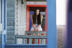 Mulher que senta-se na balaustrada da casa de praia fotografia de stock