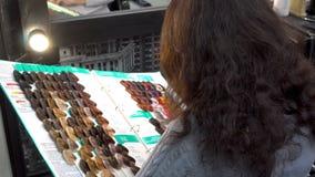 A mulher que senta-se na barbearia na frente do espelho e do catálogo seleciona uma amostra de pintura para a coloração de cabelo video estoque