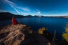 Mulher que senta-se na borda de um penhasco que olha o lago Oreg crater Foto de Stock