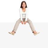 Mulher que senta-se na borda do sinal do quadro de avisos Fotografia de Stock