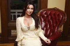 Mulher que senta-se na cadeira Fotografia de Stock