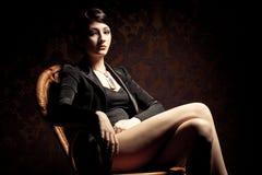 Mulher que senta-se na cadeira de madeira Fotografia de Stock Royalty Free
