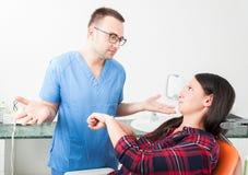 Mulher que senta-se na cadeira do dentista que mostra sendo gesto atrasado foto de stock