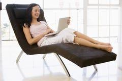 Mulher que senta-se na cadeira usando o portátil Imagens de Stock