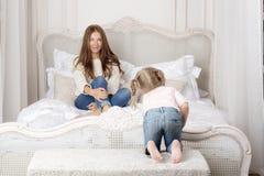 Mulher que senta-se na cama e que olha o bebê Foto de Stock Royalty Free