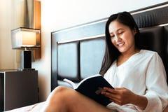 Mulher que senta-se na cama que lê o livro fotos de stock royalty free