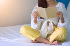 Mulher que senta-se na cama que lê um livro no quarto fotografia de stock