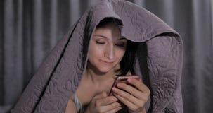 Mulher que senta-se na cama sob a cobertura e que aprecia a conversa ao amigo no smartphone imagens de stock