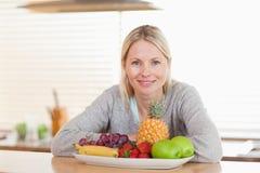 Mulher que senta-se na cozinha com uma placa dos frutos Foto de Stock Royalty Free