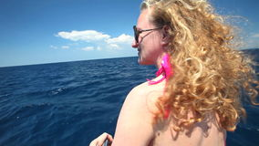 Mulher que senta-se na curva do barco de navigação que aprecia a vista do mar filme