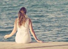 Mulher que senta-se na doca de madeira que olha para fora no oceano Imagem de Stock Royalty Free