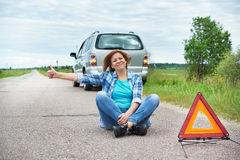 Mulher que senta-se na estrada perto do sinal da emergência que mostra os polegares acima Imagens de Stock Royalty Free